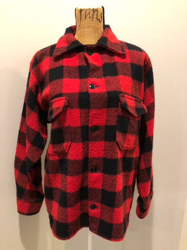 Red plaid lumberjack shirt with button closures and two flap pockets on the chest.