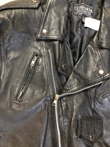 Cosa Nova black leather motorcycle jacket with two slash pockets, one flap pocket and a belt at the waist. Made in Canada. Size large.