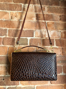 Dark brown reptile handbag with top handle, brass hardware, push button front clasp, detachable shoulder strap, inside pockets and leather lining.