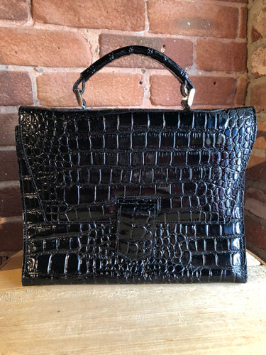 Remo black shiny reptile handbag with top handle, magnetic front closure, suede lining with inside divider pocket and change pocket.
