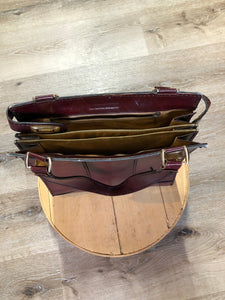 Caggiano deep red calfskin leather purse with brass hardware, two buckles on each side to allow the top to open fully, inside dividers and pockets. Made in Italy.