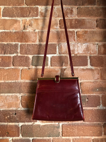 Kingspier Vintage - Deep red leather handbag circa 1950's with brass metal details and clasp.