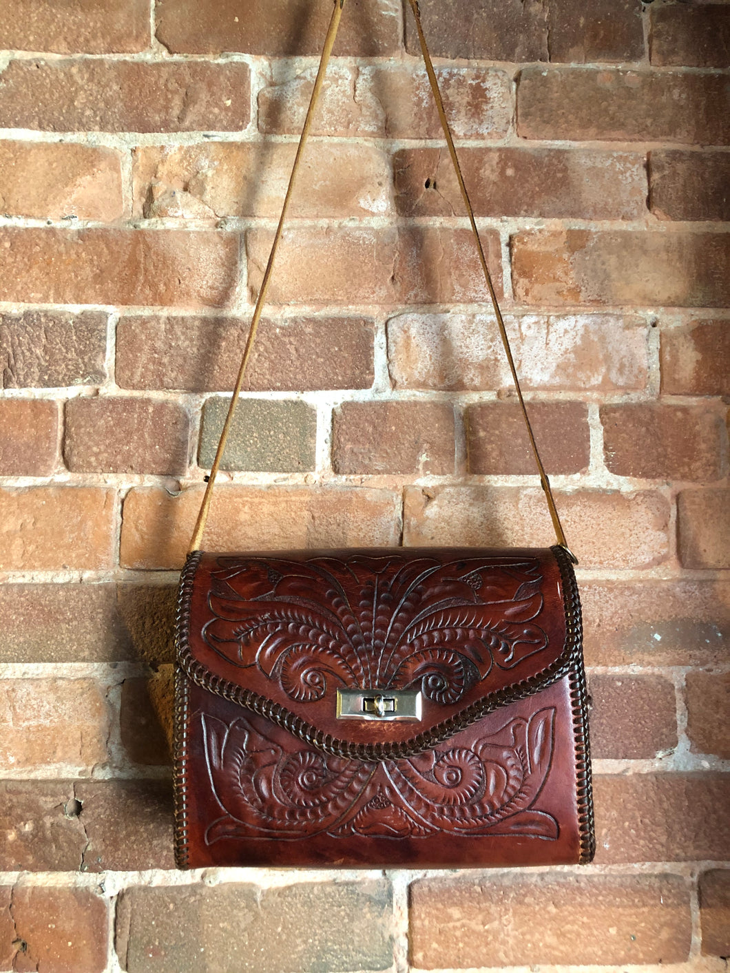 Hand tooled brown leather purse with leather stitching around the trim and a red leather flower motif lining.