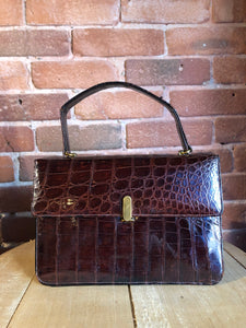 Bellestone red/brown lizard handbag, circa 1970's with top handle, leather lining, brass hardware and clasp closure.