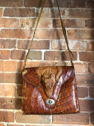 Rare brown reptile handbag with full alligator body detail, silver hardware, adjustable strap, leather lining and one inside zip pocket.