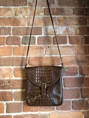 Brahmin croc-embossed leather crossbody handbag in pecan brown. This bag features brass hardware, snap buckle closure, back pocket and inside zip pocket. Made in the USA.