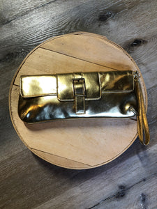 Danier gold leather flap clutch with magnetic buckle closure, inside zip pocket and wrist strap.