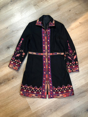 "Black wool car coat with purple and pink flower motif embroidery, snap closures, and pockets. Size small/ medium.  Shoulder to shoulder - 17"" Shoulder to wrist - 24"" Under sleeve - 17.5"" Armpit to armpit - 19"" Armpit to hem - 27"" Bottom hem - 24""  *All items have been laid flat to measure.  This coat is in excellent condition."