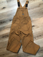 Load image into Gallery viewer, Kingspier Vintage - Berns sleeveless duck canvas overalls in tan brown. Overalls feature adjustable shoulder straps with buckle fastening, hammer loop, patch pocket on the chest, side utility pockets, pockets in the front and back, overalls button at the waist and have reinforced knees. Size 32X32.