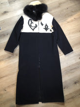 Load image into Gallery viewer, Linda Lundstrom full length black and white wool coat with fur hood, soft leather applique on the chest and back, zipper closures and a black satin like lining. Made in Canada.
