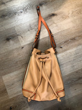 "Load image into Gallery viewer, KGB Orange and peach leather bucket bag with drawstring top closure, adjustable strap and side zip pockets.  Length - 11.5"" Width - .5.5"" Height - 13.5"" Strap - 32"" - 29""  This purse is in great condition with some wear in the strap."