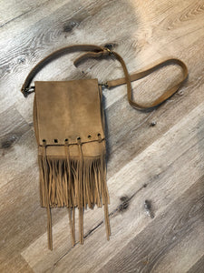 Suede crossbody bag with fringe, adjustable strap and snap closure.