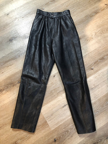 Black leather highrise pleated pants with tapered leg and front pockets