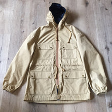 Load image into Gallery viewer, Kingspier Vintage - 1960s Vintage Zero King storm jacket in beige with hood, zipper closure, four flap pockets on the front, drawstring at the waist. Made in USA. Size 44.
