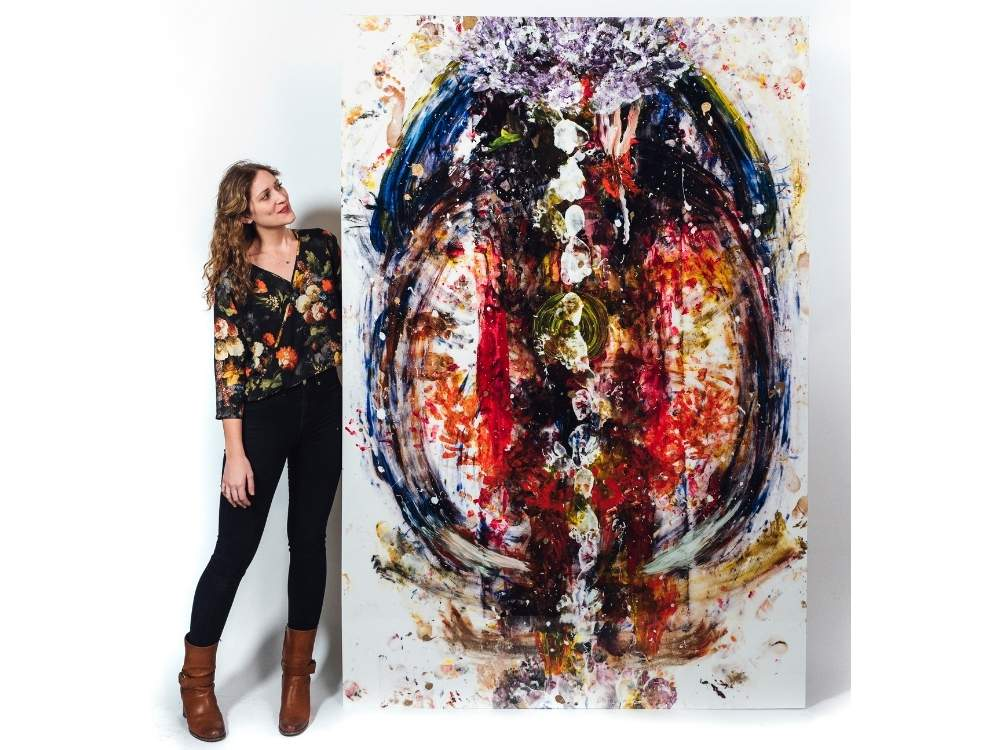 A woman stands next to an abstract painting that is taller than she is.