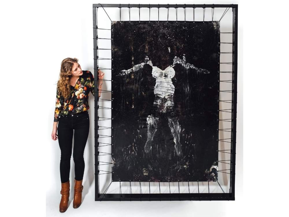A woman stands next to a large, black artwork, feet taller than she is. The frame around the piece is connected to the artwork by pieces of black rope, it almost looks like a trampoline. Inside, there is a white print of the artists body.