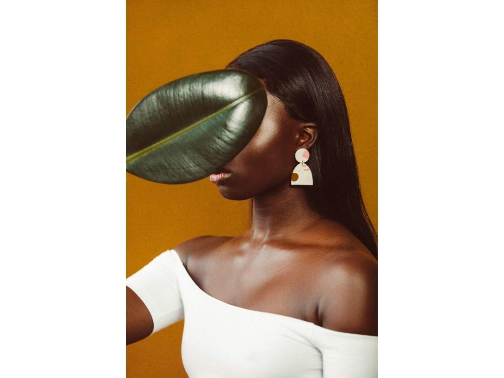 A woman's face is covered by a large leaf.