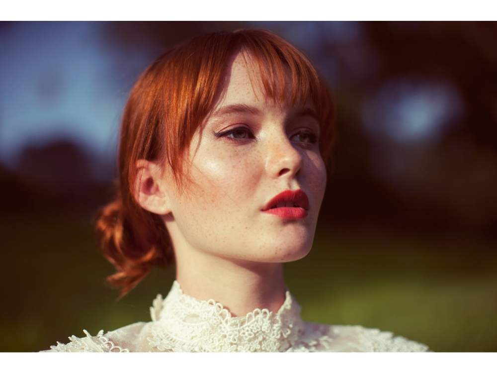 A woman with red hair, a white collared shirt, and pink lipstick looks off into the distance.