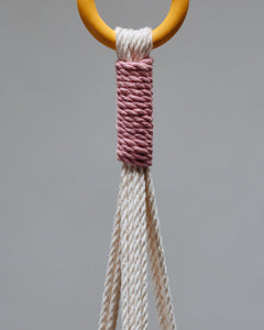 Macrame indoor trailing plant hook and pale pink and off-white woven threads.