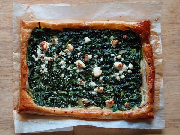 Spinach puff pastry tart with crumbled feta topping