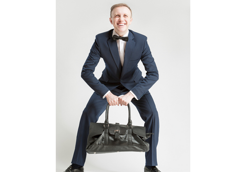 man in suit struggling to carry his office bag