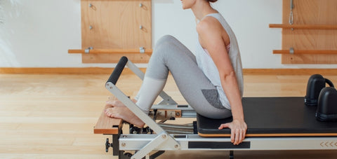 A pilates reformer with a built in platform extension at the front end