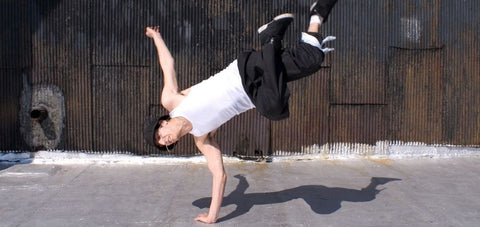 breakdancer showing a move that supports with one hand