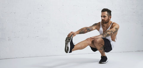 pistol squat done at the bottom position holding the toes of the front leg