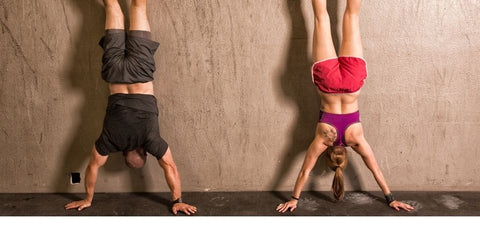 a man and a lady doing wall handstands