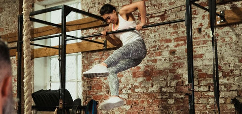 lady forcing herself to do a muscle up with the elbow flaring out and going over the bar one shoulder at a time