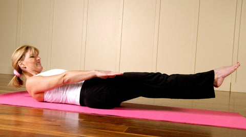 A lady doing Pilates hundreds with the legs close to horizontal position