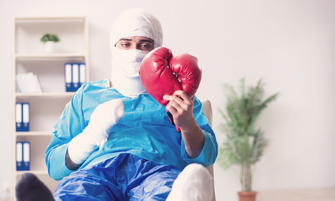 Heavily bandaged injured man looking at his boxing gloves wishing when he can go back to training