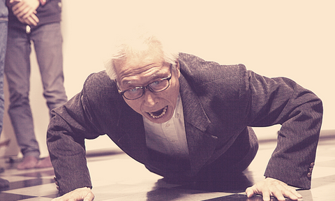 Old guy in suit struggling to do push up and doing it in the wrong form