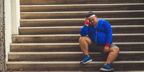 overweight man seated on the stairs tired and frustrated with not progressing with his training