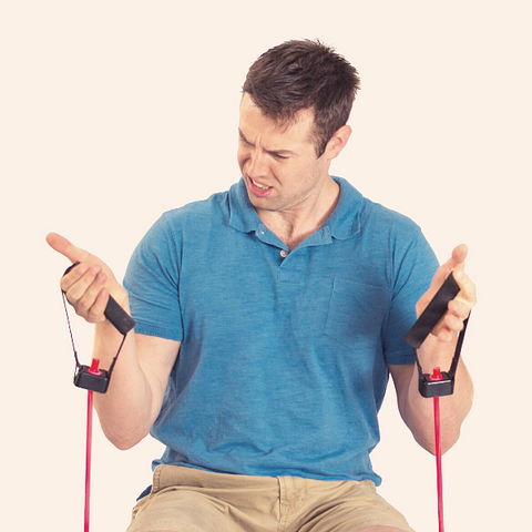 Man struggling to pull elastic bands. Signs of weakness with his program not working.