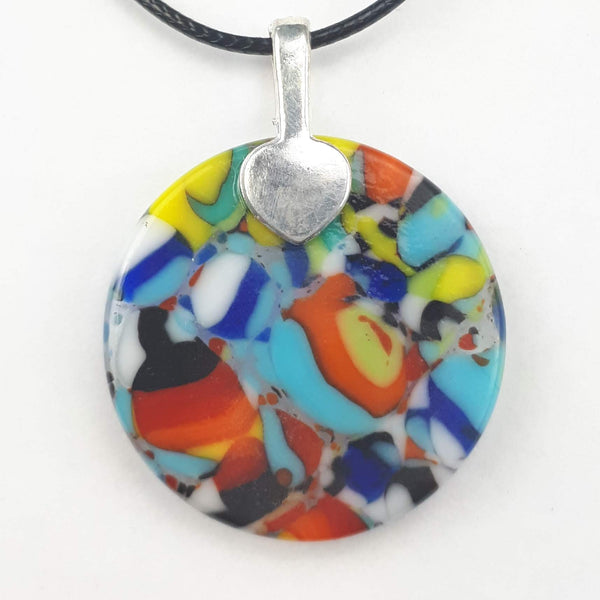 back of multicoloured round glass pendant on white background
