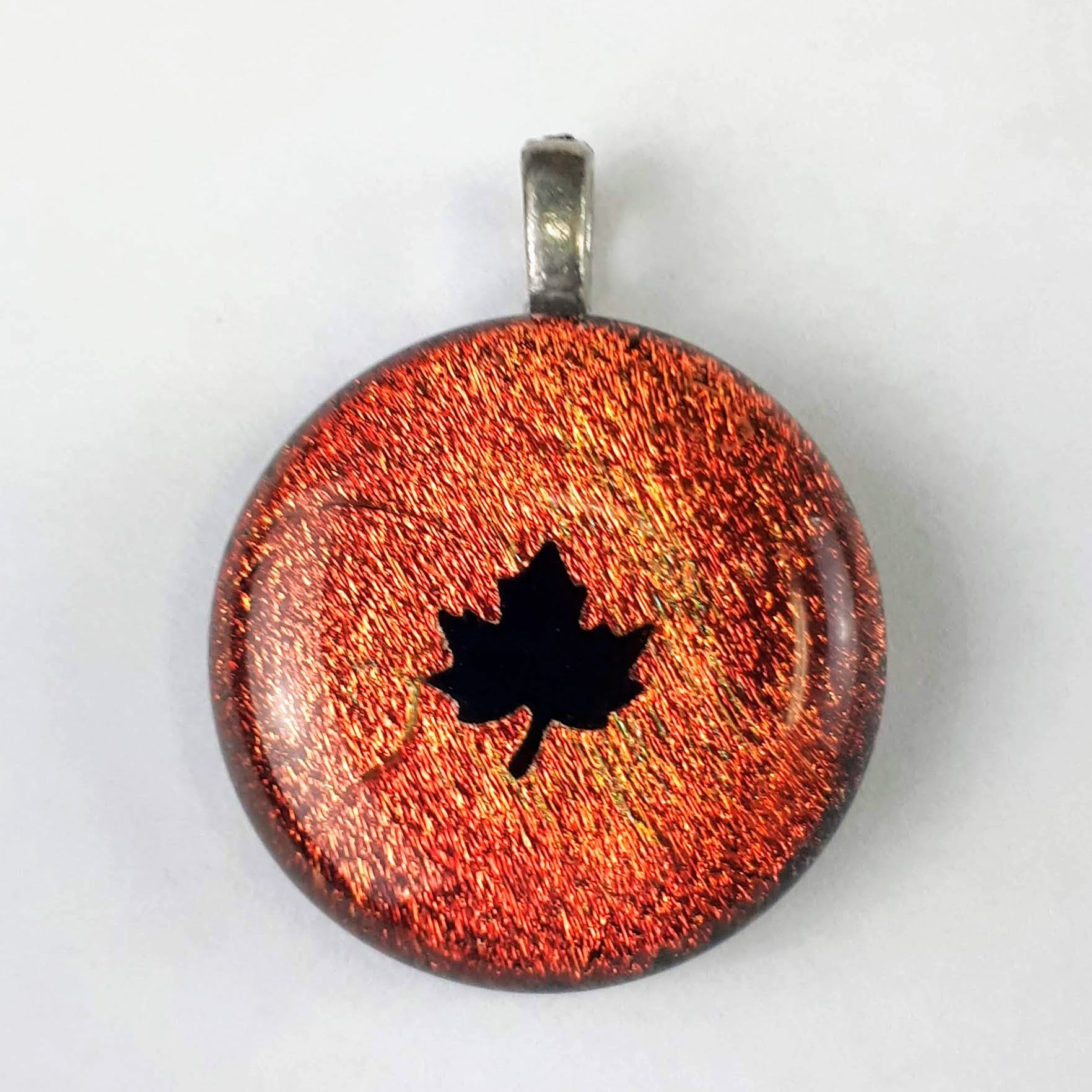 Sparkly orange and black maple leaf glass pendant on white background
