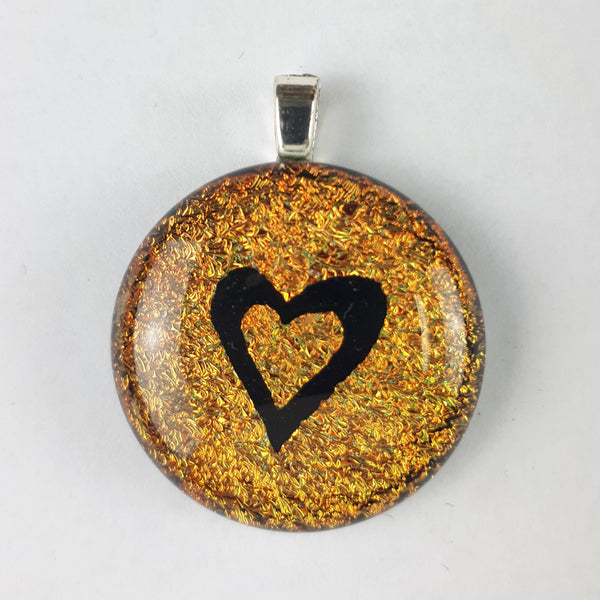 Sparkly gold and black heart glass pendant on white background