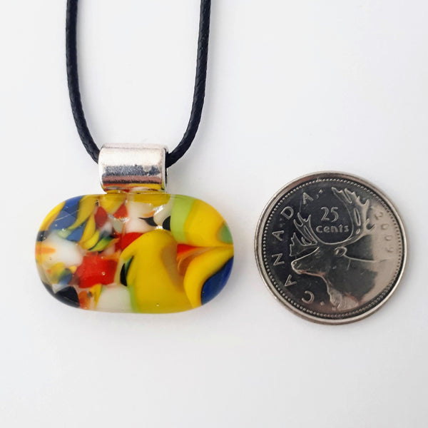 Wide oval glass fused necklace pendant with colourful blue, red, yellow, with small bits of green and white chunks/specs in it, with silver coloured bail and black cord on white background with a quarter for scale