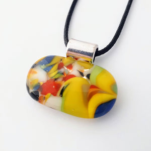 Wide oval glass fused necklace pendant with colourful blue, red, yellow, with small bits of green and white chunks/specs in it, with silver coloured bail and black cord on white background