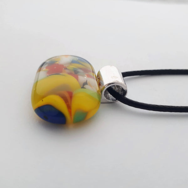 Wide oval glass fused necklace pendant with colourful blue, red, yellow, with small bits of green and white chunks/specs in it, with silver coloured bail and black cord on white background side view