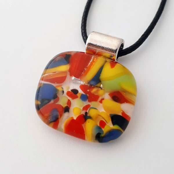 Square-ish oval glass fused necklace pendant with colourful blue, red, yellow, with small bits of green, black and white chunks/specs in it, with silver coloured bail and black cord on white background