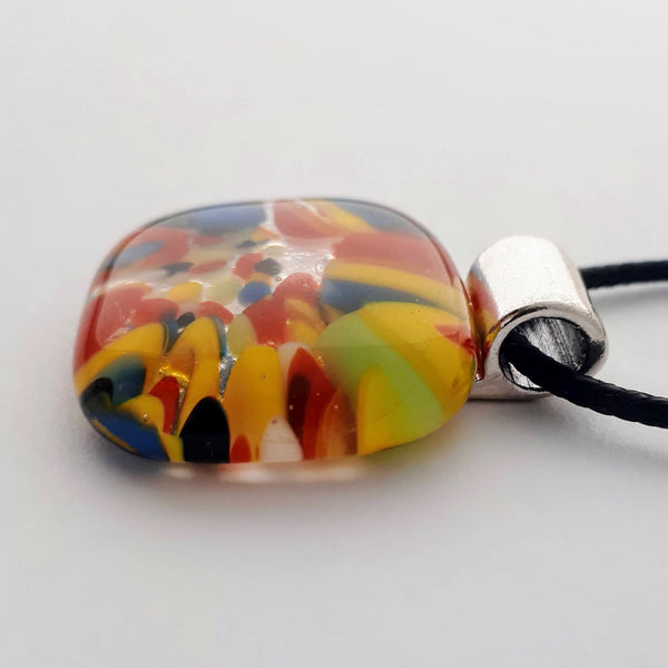 Square-ish oval glass fused necklace pendant with colourful blue, red, yellow, with small bits of green, black and white chunks/specs in it, with silver coloured bail and black cord on white background side view