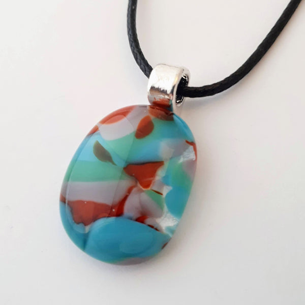 Red, Blue, Green, and purple oval glass fused pendant with silver bail and black cord on white background