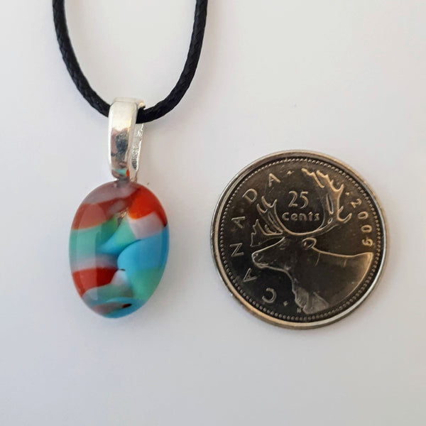 Red, Blue, Green, and purple oval glass fused pendant with silver bail and black cord on white background with quarter for scale