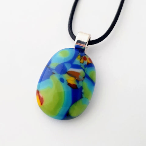 Mainly blue and green multicoloured oval glass necklace pendant on white background with black cord and silver coloured bail