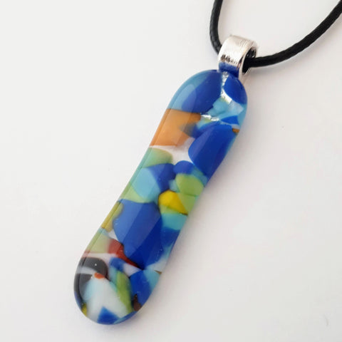 Mainly blue and green multicoloured long skinny glass necklace pendant on white background with black cord and silver coloured bail