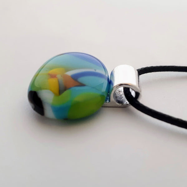 Mainly blue and green multicoloured wide oval glass necklace pendant on white background with black cord and silver coloured bail side view