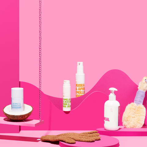 Coconut & Probiotics Deodorant in coconut on a pink swing plus various bodycare products strewn around pink props