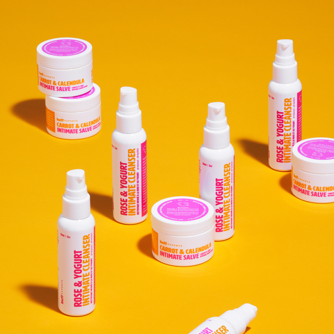 Rose & Yogurt Intimate Cleanser, Carrot & Calendula Intimate Salve on a pink table with a pink cadle, some red candies and a red lace bra